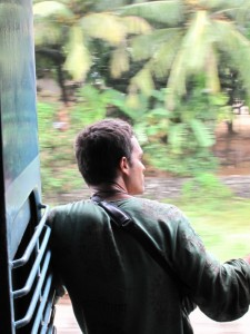 Watching the world pass by from the doorway of a train