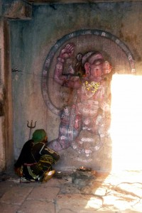 A baba worships at a carving of Hanuman, Hampi