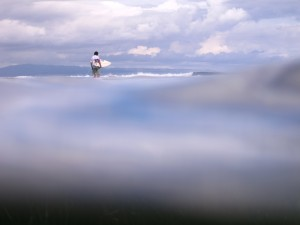 Lone surfer walking across to the break at Serangan Island